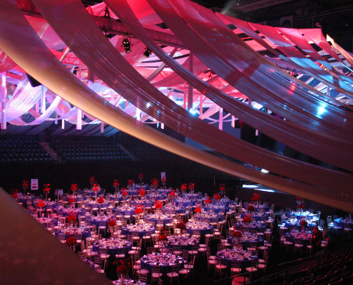 This arena was transformed into an elegant event with an intricate ceiling draping scheme and dynamic lighting that shifted through the evening for a corporate centennial celebration.