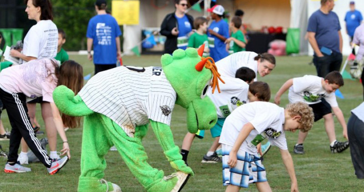 As part of a community festival, teen boys from the Let Me Run program and their coaches warming up with Charlotte Knights mascot Homer before their 5K race.